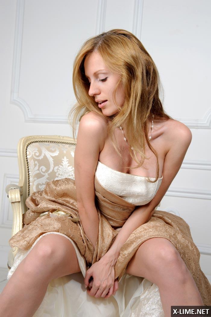 Голая пышногрудая девушка позирует на белом кресле, эротические фото
