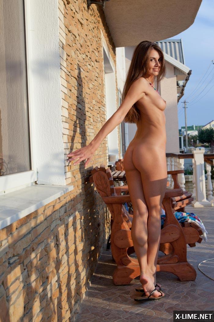 Голая шатенка сексуально позирует на террасе