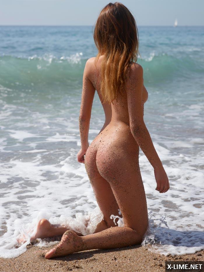 Голая рыжая девушка на берегу моря