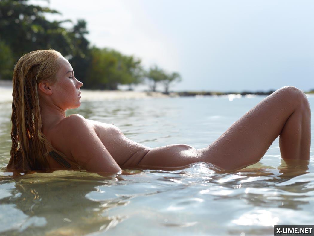 Голая девушка с веснушками на берегу океана