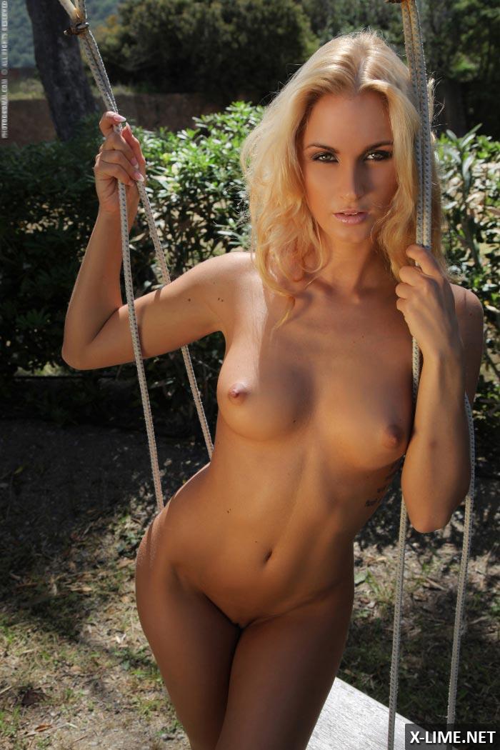 Голая стройная блондинка позирует на качелях
