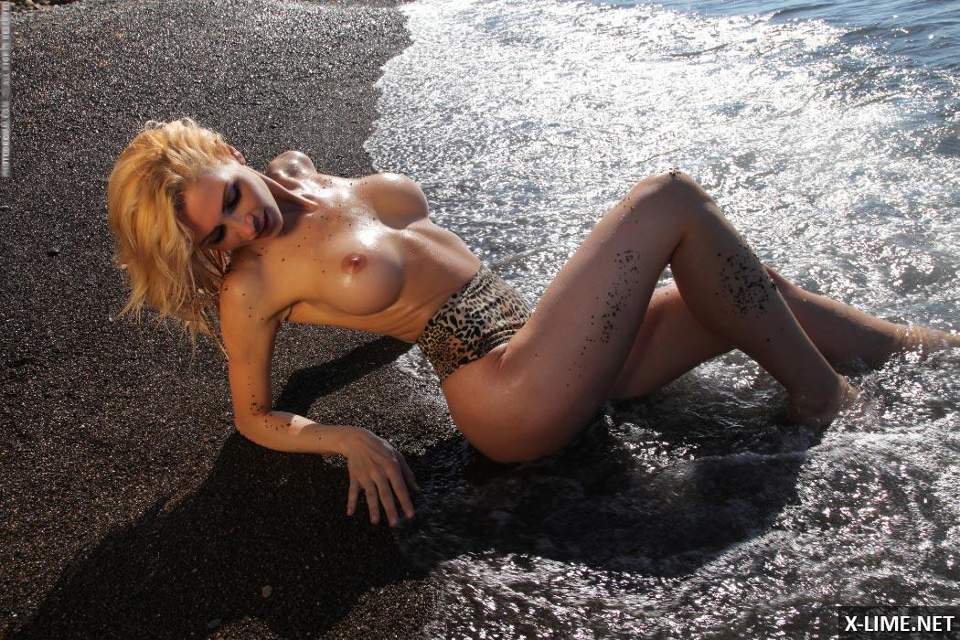 Голая пышногрудая блондинка на пляже