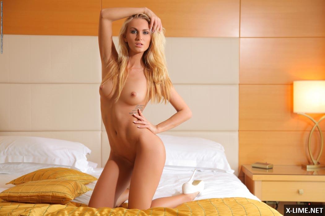 Голая блондинка позирует в спальне