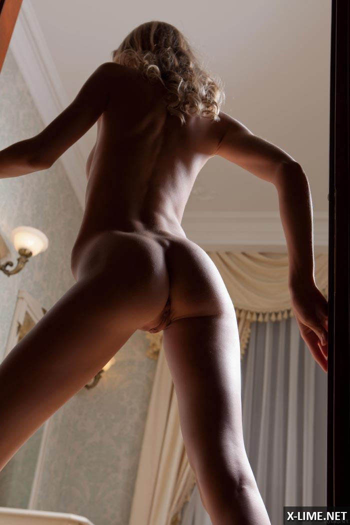 Симпатичная блондинка позирует голой на диване