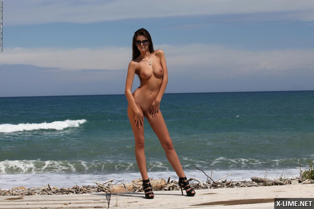 Голая девушка гуляет по пляжу