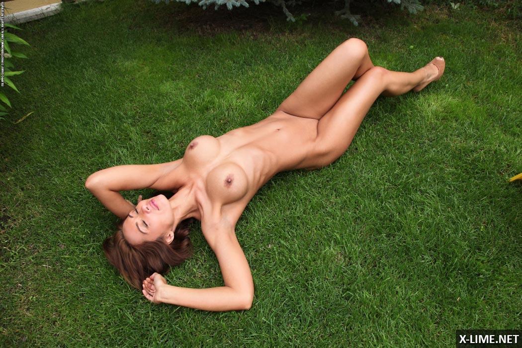 Худая с большими сиськами лежит на траве